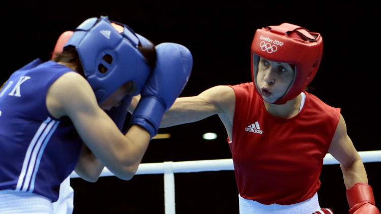 Russia's Elena Savelyeva, right, lands a punch against North Korea's Kim Hye Song, during the women's flyweight boxing competition at the 2012 Summer Olympics, Sunday, Aug. 5, 2012, in London. (AP Photo/Ivan Sekretarev)