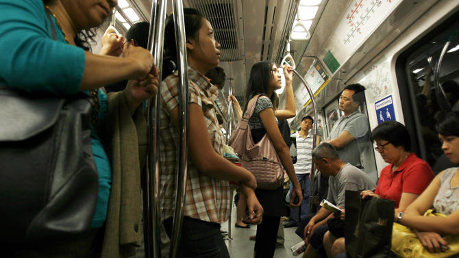 FILE - In this Feb. 22, 2010 file photo, commuters make their way to work on a train in Singapore. Already one of the most densely populated countries in the world, tiny land scarce Singapore is projecting its population to swell by a third over the next two decades. To accommodate the influx, its planners envisage expanding upward, outward and downward. The population target of 6.9 million people, an increase of 1.3 million from the present, is contentious in a country where rapid immigration has already strained services such as public transport and contributed to a widening wealth gap. (AP Photo/Wong Maye-E, File)