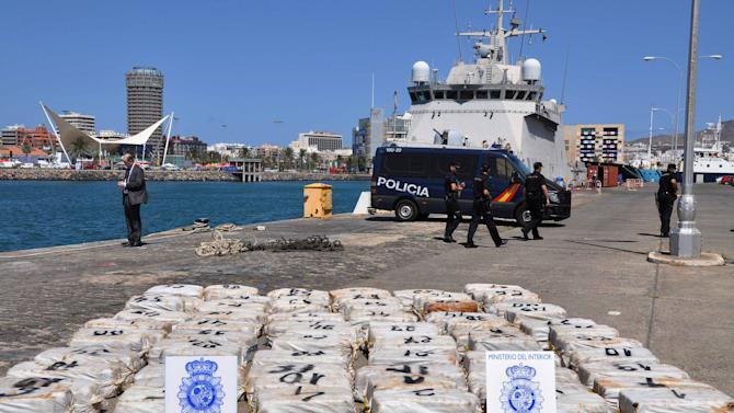In this photo made available by the Spanish police Saturday, March 23, 2013, police stand guard over bags containing cocaine at the harbor of Las Palmas de Gran Canaria, Spain. The Interior Ministry says Spanish, Portuguese and British police have boarded in the Atlantic a ship that was loaded with nearly two tons of cocaine destined for sale in Europe, and arrested nine people. (AP Photo/Spanish Police)