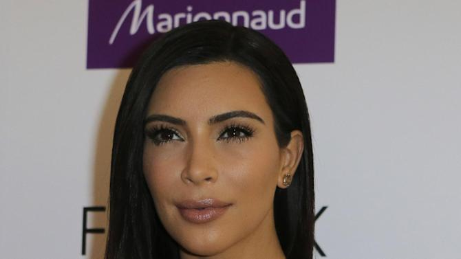 "FILE - In a Wednesday, April 15 2015 file photo, Kim Kardashian attends a photocall to launch hair products in Paris. Kardashian said during an appearance on NBC's ""Today"" show on Monday, April 27, 2015, that she and her family support her stepfather Bruce Jenner 100 percent as he goes through gender transition, even though family members are still adjusting to that news in what she called ""a daily process.""(AP Photo/Jacques Brinon, File)"