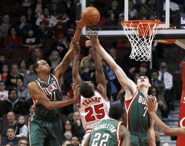 Milwaukee Bucks forward John Henson, left, blocks the shot of Chicago Bulls point guard Marquis Teague (25) as Ersan Ilyasova (7) also defends during the first half of an NBA basketball game Tuesday,
