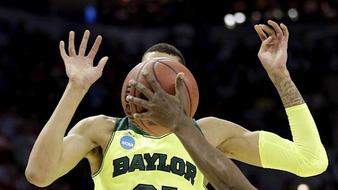 Baylor's Isaiah Austin (21) has his face covered by the ball as Nebraska's Leslee Smith's arm reaches for the ball during the second half of a second-round game in the NCAA college basketball tournament Friday, March 21, 2014, in San Antonio. Baylor won 74-60