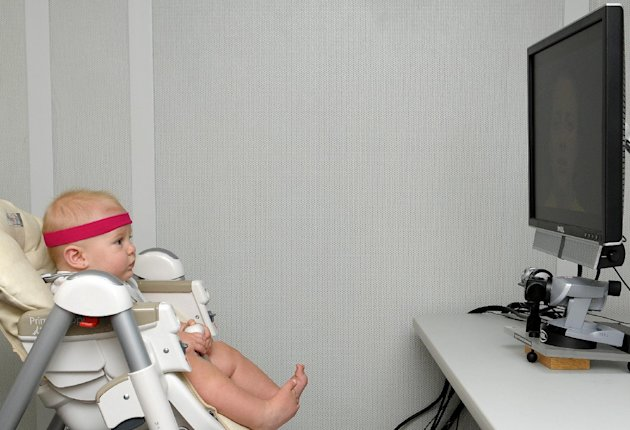 "This undated handout photo provided by Florida Atlantic University shows a baby, looking at a monitor, wearing a band that contains a little magnet that the head-tracker, under the monitor uses to determine head position which, in turn, enables the eye tracker to find the eye and the pupil. New research suggests babies don't learn to talk just from hearing sounds _ they're lip-readers, too. It happens during that magical stage when a baby's babbling gradually changes from gibberish into syllables and eventually into that first ""mama"" or ""dada."" (AP Photo/Florida Atlantic University)"