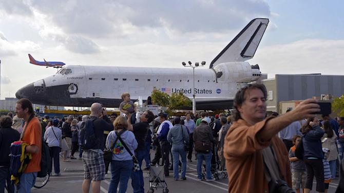 "Spectators gather around the Space Shuttle Endeavour before it is moved along city streets, Friday, Oct.12, 2012, in Los Angeles.  Endeavour's two-day, 12-mile road trip to the California Science Center, where it will be put on display,  kicked off early Friday. Rolled on a 160-wheeled carrier, it left from a hangar at the Los Angeles International Airport, passing diamond-shaped ""Shuttle Xing"" signs, and reached city streets about two hours later.  (AP Photo/Mark J. Terrill)"