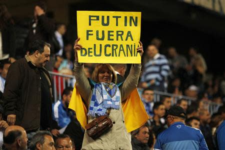 A woman with a Ukrainian flag draped around her shoulders holds a placard during the Spanish First Division match between Real Madrid and Malaga in Malaga