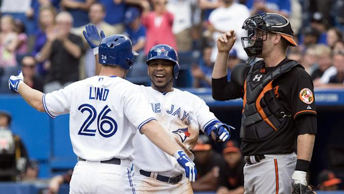 Toronto Blue Jays' Adam Lind, left, celebrates with Edwin Encarnacion after hitting a two-run homer off Baltimore Orioles starting pitcher Jason Hammel as Orioles catcher Matt Wieters looks on during the first inning of a baseball game in Toronto on Friday, June 21, 2013. (AP Photo/The Canadian Press, Chris Young)