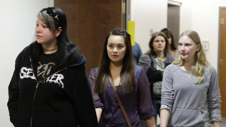 Chantel Blunk, center, holds hands with two women as they arrive for a court proceeding for Aurora theater shooting suspect James Holmes at the courthouse in Centennial, Colo., on Friday, Jan. 11,  2013. Blunk's husband Jon was killed in the theater. The judge  granted a defense motion to delay the arraignment of Holmes until March 12. The decision comes a day after the judge ruled that Holmes should stand trial. (AP Photo/Ed Andrieski)