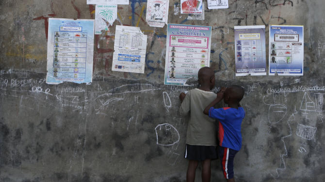 Boys draw with chalk on a wall hung with posters displaying sample ballots for the upcoming presidential, parliamentary, and local elections, in Freetown, Sierra Leone Friday, Nov. 16, 2012. Ten years after the end of a devastating civil war, Sierra Leone will go to the polls on Saturday to choose between candidates including incumbent President Ernest Bai Koroma and opposition leader Julius Maada Bio. (AP Photo/Rebecca Blackwell)