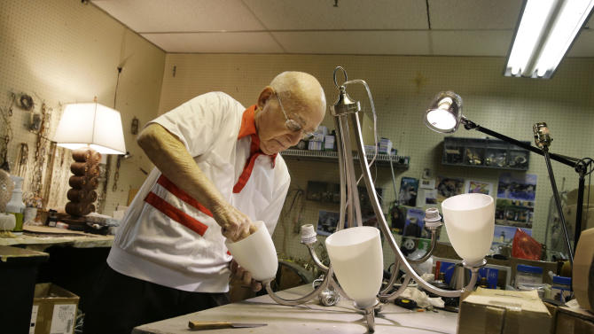 """Lighting repair specialist Herman """"Hy"""" Goldman, 101, refurbishes a light fixture in his workshop at Capitol Lighting where he has worked for 73 years, Monday, Aug. 18, 2014, in East Hanover, N.J. Now that he has turned 101, Goldman who often said that he would retire when he reached 100, has changed his mind. He still drives himself to work four days a week. (AP Photo/Mel Evans)"""