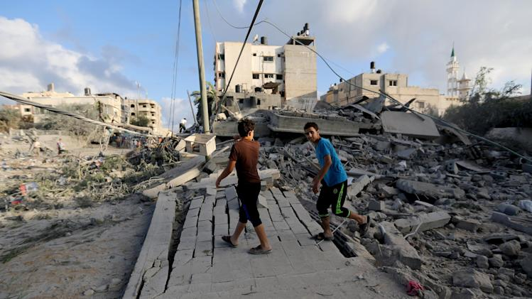 Palestinians walk on the rubble of a building damaged in an Israeli airstrike in Gaza City, Friday, July 25, 2014. Early Friday, Israeli warplanes struck tens of houses throughout the Gaza Strip as international efforts continue to broker a cease-fire in the 18-day-old war. (AP Photo/Hatem Moussa)