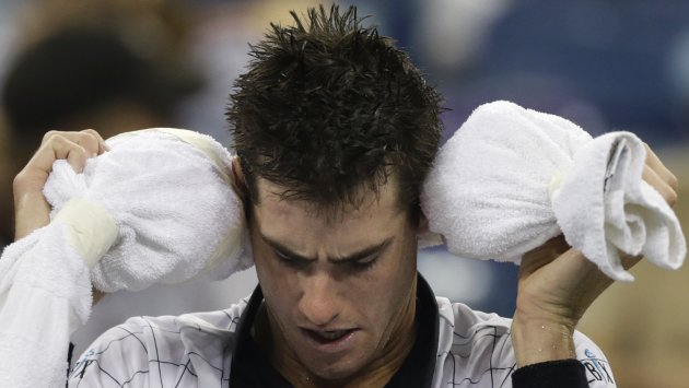 John Isner wraps his head with ice wrapped in a towel during his match with Philipp Kohlschreiber, of Germany, in the third round of play at the 2012 US Open tennis tournament, early Monday, Sept. 3, 2012 in New York. The match began on Sunday evening. (AP Photo/Charles Krupa)