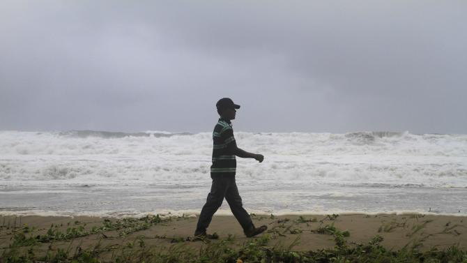 A resident walks along Los Yayales beach as strong waves crash due to the approach of Hurricane Irene to Nagua, in the northern coast of the Dominican Republic, Monday, Aug, 22, 2011. Hurricane Irene churned into a stronger Category 2 storm on Monday evening, after raking Puerto Rico with strong winds and rain that knocked out power to more than a million people, on a track that could carry it to the U.S. Southeast as a major storm by the end of the week. (AP Photo/Roberto Guzman)
