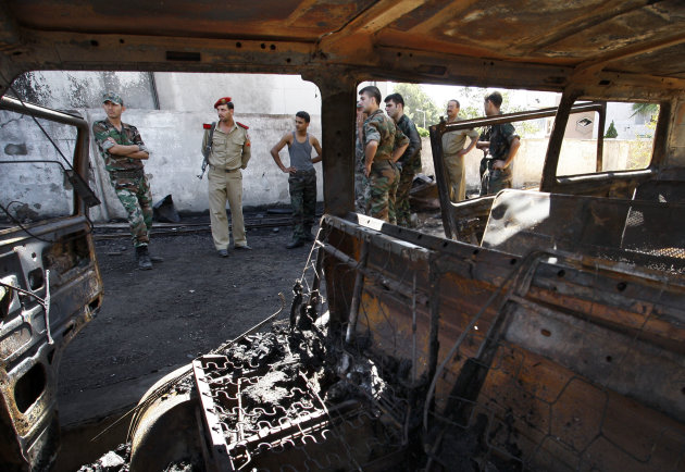 Syrian soldiers investigate the scene after a bomb attached to a fuel truck exploded outside a Damascus hotel where U.N. observers are staying in Damascus, Syria, Wednesday, Aug. 15, 2012. Several people were wounded, Syria&#39;s state TV reported. TV said the explosion took place near a parking lot used by the army command, which is about 300 meters (yards) away. (AP Photo/Muzaffar Salman)