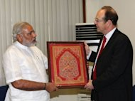 Britain's ambassador to India James Bevan (R) receives a gift from Gujarat state chief minister Narendra Modi during a meeting in Gandhinagar, some 30 kms from Ahmedabad, on October 22, 2012, in a handout image from the Gujarat Information Bureau. Britain held talks Monday with Modi, ending a 10-year boycott over deadly religious riots in Gujarat state that left more than 2,000 dead