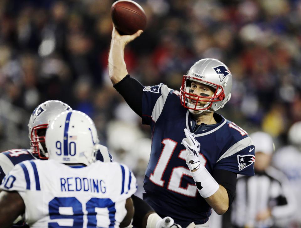 New England Patriots quarterback Tom Brady (12) throws the ball as Indianapolis Colts defensive end Cory Redding (90) tries to defend in the first quarter of an NFL football game at Gillette Stadium in Foxborough, Mass., Sunday, Nov. 18, 2012. (AP Photo/Charles Krupa)