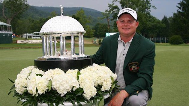 Ted Potter, Jr. kneels with the championship trophy after winning the Greenbrier Classic