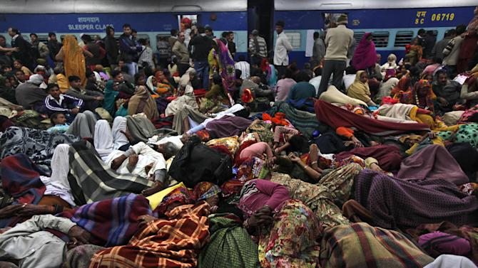 Indian pilgrims sleep on a railway platform in Allahabad, India, Sunday, Feb. 10, 2013. At least ten Hindu pilgrims attending the Kumbh Mela were killed and more then thirty were injured in a stampede on an overcrowded staircase, according to Railway Ministry sources. (AP Photo/Rajesh Kumar Singh)