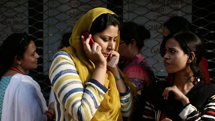 A Pakistani woman speaks on her mobile phone after rushing out of her apartment following a major earthquake that struck Baluchistan province in southwest Pakistan, 693 Kilometers (430 miles) from Karachi, Pakistan, Tuesday, Sept. 24, 2013. A deadly earthquake struck Tuesday in southwestern Pakistan sending poeople fleeing into the streets and praying for their lives as buildings swayed, officials said. (AP Photo/Shakil Adil)