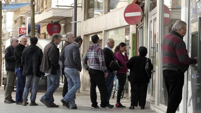 People queue outside a Laiki bank branch as a man receives money from an ATM machine in capital Nicosia, on Friday, March 29, 2013.  Banks in Cyprus are open for normal business for the second day, but with strict restrictions on how much money their clients can access, after being shut for nearly two weeks to prevent people from draining their accounts as the country's politicians sought a way out of an acute financial crisis.(AP Photo/Petros Giannakouris)
