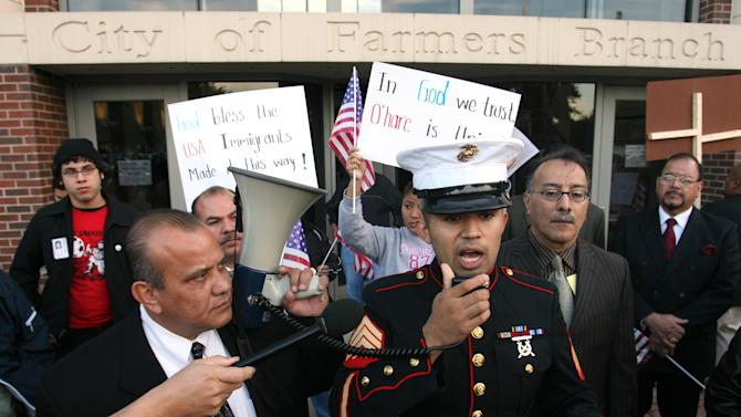 FILE - In this Nov. 13, 2006 file photo, former Marine Sgt. Salvadaor Parada, right, speaks to protesters during a rally outside city hall in Farmers Branch, Texas.  A federal appeals court will review Farmers Branch's ordinance, which allows the city building inspector to evict any illegal immigrant renters. (AP Photo/Rex C. Curry, File)