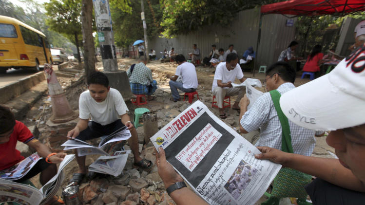 "A man reads a local daily newspaper with its front page printed black with letters saying ""By opposing recent arrest and sentencing of journalists including a video journalist of DVB (Democratic Voice of Burma)"" with others near a roadside shop Friday, April 11, 2014, in Yangon, Myanmar. Several private newspapers in Myanmar printed black front pages on Friday to protest the recent arrests and sentencing of journalists, in the latest sign the country's media climate is worsening. (AP Photo/Khin Maung Win)"