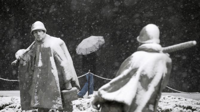 A visitor to the Korean War Veterans Memorial shields himself from the falling snow in Washington