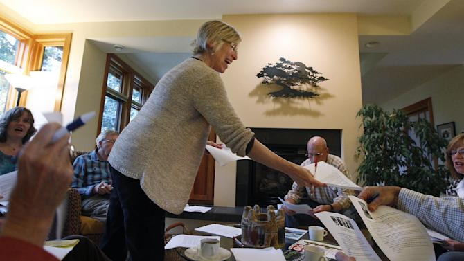 In this photo taken Tuesday, Oct. 23, 2012, Cindy Franklin hands out information about how to write letters against a proposed coal exporting facility, in her home in Bellingham, Wash. The progressive college town of Bellingham is at the center of one of the fiercest environmental debates in the region: should the Northwest become a hub for exporting U.S. coal to Asia? A proposal to build one of as many as five coal terminals here has divided the town, pitting union and businesses that welcome jobs against environmentalists who worry about coal dust and greenhouse gas emissions. A trade group is running TV ads touting the projects, while numerous cities such as Seattle and Portland are opposing coal trains through their communities. (AP Photo/Elaine Thompson)