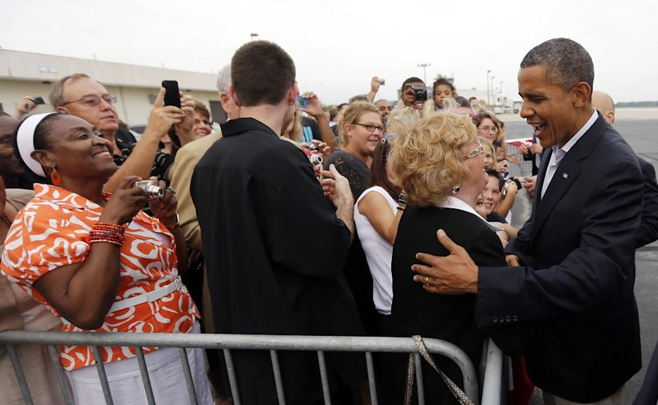 President Barack Obama, right, greets supporters on the tarmac upon his arrival at Toledo Express Airport, Sunday, Sept. 2, 2012, in Toledo, Ohio. (AP Photo/Pablo Martinez Monsivais)