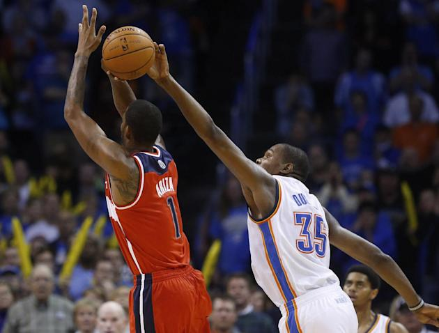 Oklahoma City Thunder forward Kevin Durant (35) blocks a shot by Washington Wizards forward Trevor Ariza (1) in overtime of an NBA basketball game in Oklahoma City, Sunday, Nov. 10, 2013. Oklahoma Cit