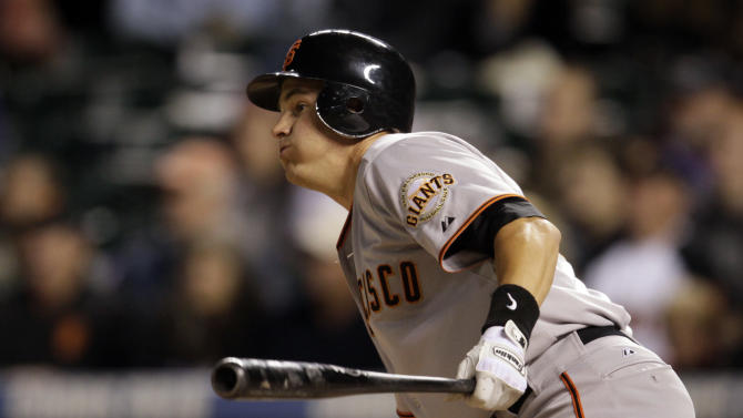 San Francisco Giants' Brett Pill watches his fly ball hit to centerfield, scoring two base runners during the eighth inning of a baseball game in Denver, on Saturday, Sept. 17, 2011. (AP Photo/Joe Mahoney)