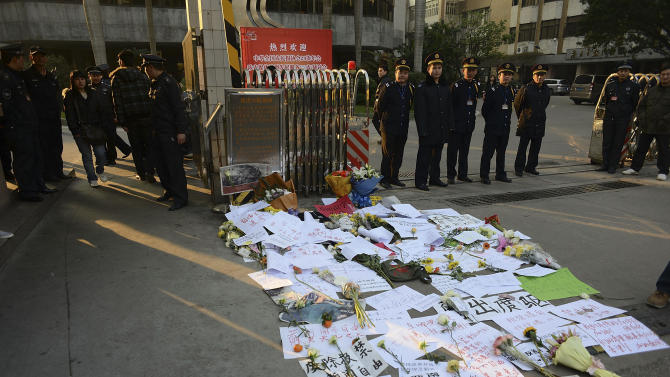 Security guards stand near protest banners and flowers are laid outside the headquarters of Southern Weekly newspaper in Guangzhou, Guangdong province Monday, Jan. 7, 2013. A dispute over censorship at the Chinese newspaper known for edgy reporting evolved Monday into a political challenge for China's new leadership as prominent scholars demanded a censor's dismissal and hundreds of protesters called for democratic reforms.  (AP Photo)