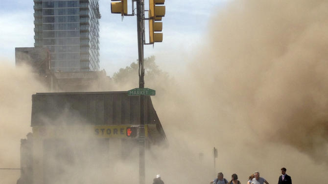 In this photo provided by Jordan McLaughlin, a dust cloud rises as people run from the scene of a building collapse on the edge of downtown Philadelphia on Wednesday, June 5, 2013.  Buoyed by the discovery of a woman buried in rubble nearly 13 hours later, rescue workers on Thursday were digging through the debris from the building collapse that killed six people a day earlier.  (AP Photo/Jordan McLaughlin)