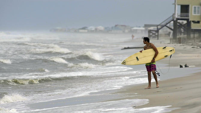 A surfer waits with his board to surf Thursday, Sept. 1, 2011, in Dauphin Island, Ala. Forecasters have issued tropical storm warnings for the U.S. Gulf coast from Mississippi to Texas as a depression has organized in the Gulf of Mexico. (AP Photo/Mobile Press-Register, G.M. Andrews)  NO SALES; MAGS OUT