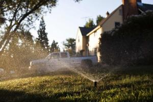 File of a sprinklers spraying water at a home on a …