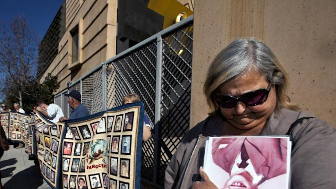 "Survivor Angie Story, 67, right, holds on to a picture of ""Eric,"" a victim of sexual abuse who committed suicide, as members of SNAP, the Survivors Network of those Abused by Priests, before holding a news conference outside the Cathedral of Our Lady of the Angels in Los Angeles, Friday, Feb. 1, 2013. Cardinal Roger Mahony of the largest Roman Catholic archdiocese in the United States was stripped of his duties in an unprecedented move by his successor Archbishop Jose Gomez, who described the church's actions during the growing sex abuse scandal as evil.  (AP Photo/Damian Dovarganes)"