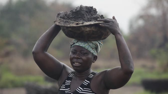 Koffi Cecile, 40, carries spent dirt away after drawing out salt from it in the village of Djegbadji near Ouidah, Benin, on Friday, Jan. 11, 2013. Artisanal salt farmers in this village in Benin dig off the top layer of soil near their hut homes, then filter water through the dirt to draw out salt. They later boil the water to collect the salt and sell it. On average, they sell enough for two salt shakers for about $1. (AP Photo/Sunday Alamba)