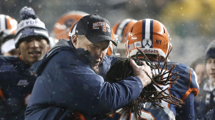 Syracuse coach Doug Marone embraces running back Prince-Tyson Gulley (23) who scored a second-quarter touchdown against West Virginia during the Pinstripe Bowl NCAA college football game at Yankee Stadium in New York, Saturday, Dec. 29, 2012. (AP Photo/Kathy Willens)