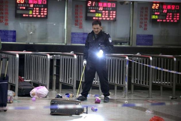 A police investigator inspects the scene of a mass stabbing at the railway station in Kunming, southwest China's Yunnan province, on March 2, 2014. (AFP photo)