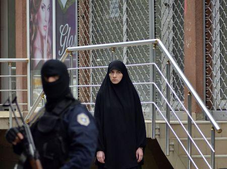 A woman looks as she walks past a police officer standing guard in front of a court in Pristina