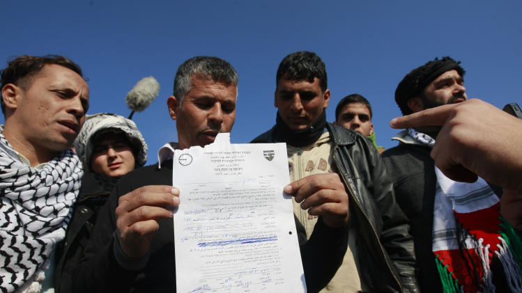 A Palestinian activist holds a sheet paper from the Israeli police ordering the immediate evacuation of the new 'outpost ' of Bab al-Shams (Gate of the Sun) in an area known as E1, near Jerusalem, Friday, Jan 11, 2013. Palestinian activists pitched tents in the West Bank on Friday to protest Israeli plans to build a large Jewish settlement on a key route through the territory. The E-1 settlement would block east Jerusalem from its West Bank hinterland — both territories captured by Israel during the 1967 Mideast war. (AP Photo/Majdi Mohammed)