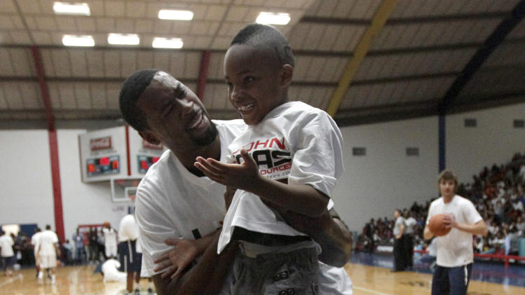 Los Angeles Clippers' DeAndre Jordan, left, holds Ky Guillory, 6, after lifting him up to dunk a basketball before the Houston Lockout Celebrity Basketball Game hosted by former player and coach John Lucas, Sunday, Nov. 20, 2011, in Houston. Several NBA players played in the event that will benefit charities including the John Lucas Foundation which helps athletes who need after care or wellness services and programs. (AP Photo/David J. Phillip)