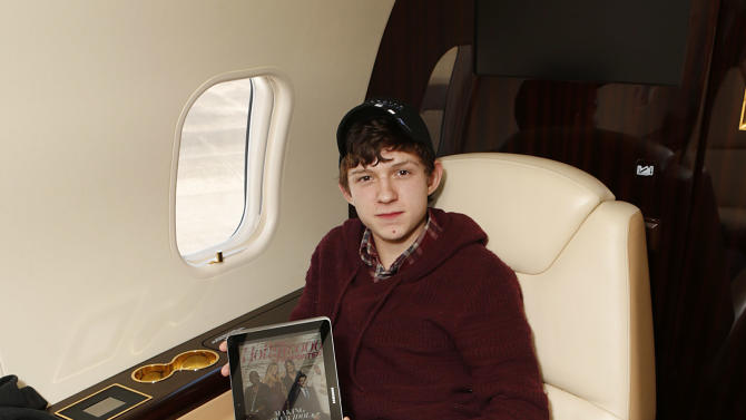 Tom Holland reads THR on a Samsung Galaxy Tablet at The Hollywood Reporter's Palm Springs Shuttle presented by Bombardier Business Aircraft - Day 2, on Saturday, January 5, 2013 in Palm Springs, California. (Photo by Todd Williamson/Invision for Bombardier/AP Images)