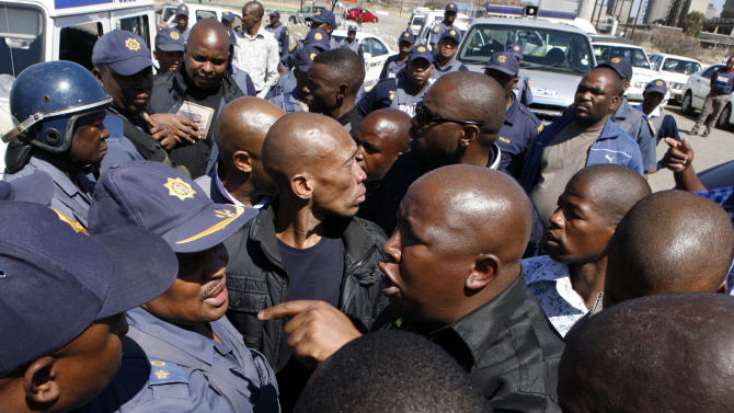 Firebrand politician Julius Malema, right argues with police officers, at Lonmin Platinum Mine near Rustenburg, South Africa, Monday, Sept. 17, 2012. London-registered Lonmin PLC announced it is halting construction of a new shaft, putting 1,200 people out of work, as the bloody and bitter strike at its beleaguered South African platinum mine dragged on its fifth week. The strikes that have halted work at seven gold and platinum mines have spread to the chrome sector, according to the official South African Press Association. Meanwhile, police blocked rabblerousing politician Julius Malema from addressing some 3,000 strikers gathered at a stadium at the Lonmin mine at Marikana, northwest of Johannesburg. (AP Photo/Themba Hadebe)