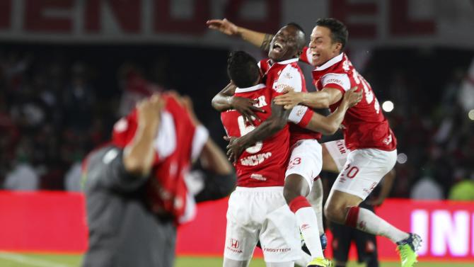 Santa Fe's Yulian Anchico, Jefferson Cuero and Juan Manuel Seijas celebrate after winning against Medellin in their final soccer match during the Colombian first division championship in Bogota