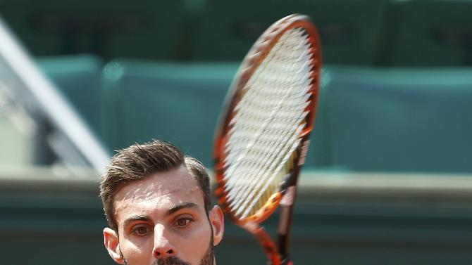 Marcel Granollers of Spain plays a shot to Roger Federer of Switzerland during their men's singles match at the French Open tennis tournament at the Roland Garros stadium in Paris