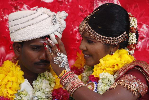 A former LTTE female rebel fighter and her groom attend a mass wedding ceremony in Kilinochchi