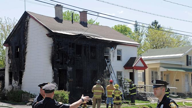 Firefighters and family members gather at the scene of a fatal fire in Utica, N.Y., Monday, May 9, 2011. A woman and three children were killed.  (AP Photo/Steve Jacobs)