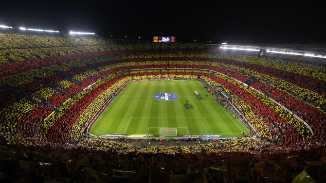 """FILE- In this Oct. 7, 2012 file photo, Barcelona supporters show colors of a giant Catalan flag at the Camp Nou stadium during a Spanish La Liga soccer match between FC Barcelona and Real Madrid, in Barcelona, Spain. More than ever, FC Barcelona, known affectionately as Barca, lived up to its motto of being """"more than a club"""" for this wealthy northeastern region where Spain's economic crisis is fueling separatist sentiment. Barca has been seen as a bastion of Catalan identity dating back to the three decades of dictatorship when Catalans could not openly speak, teach or publish in their native Catalan language. Barcelona writer Manuel Vazquez Montalban famously called the football team """"Catalonia's unarmed symbolic army."""" (AP Photo/Andres Kudacki, File)"""
