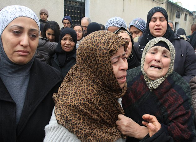 Tunisian women gather in front of the house of slain opposition leader Chokri Belaid's father prior to his funeral in Tunis, Friday, Feb. 8, 2013. Tunisia braced for clashes on Friday, with the capita