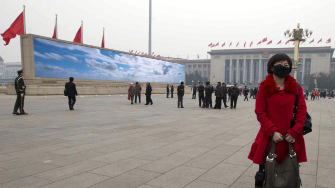 In this photo taken Wednesday, March 6, 2013 a woman wears a mask as she stands near a giant display depicting blue skies during a day of heavy pollution on Tiananmen Square in Beijing, China. Facing public outrage over smog-choked cities and filthy rivers, China's leaders are promising to clean up its neglected environment, a pledge that sets up a clash with political pressures to keep economic growth strong.  (AP Photo/Ng Han Guan)